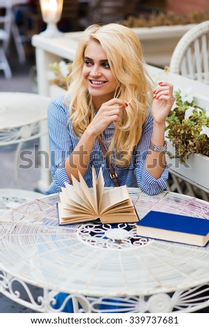 Portrait of a happy woman female with beautiful smile sitting with textbooks in coffee shop outdoors before her lectures, cheerful female enjoying good day in sidewalk cafe during recreation time  - stock photo