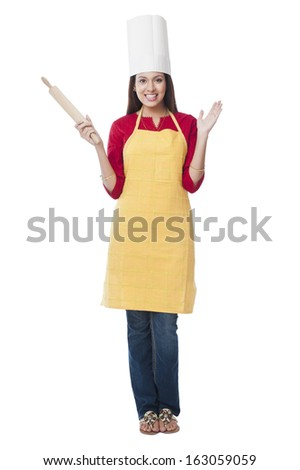 Portrait of a happy woman holding a rolling pin