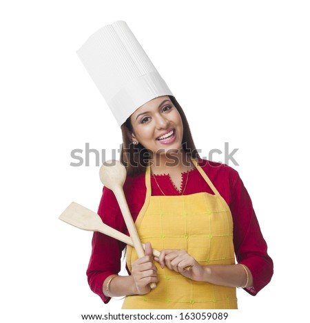 Portrait of a happy woman holding a spatula and ladle - stock photo