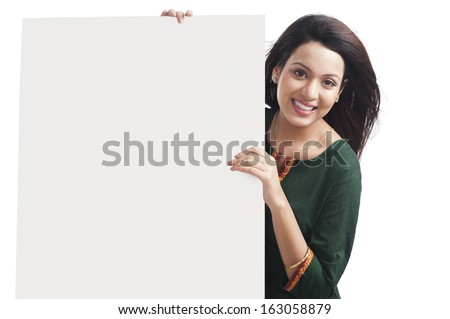 Portrait of a happy woman holding a whiteboard - stock photo