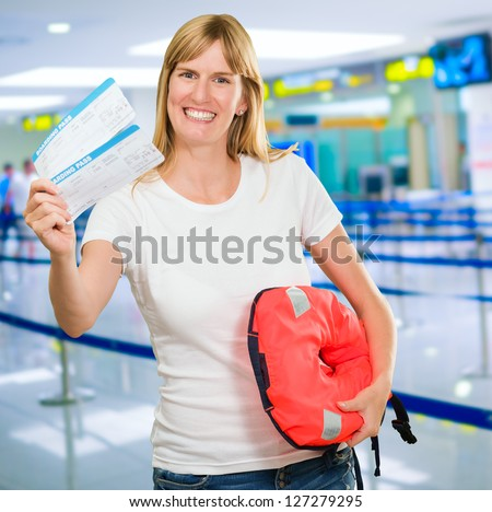 Portrait Of A Happy Woman Holding Boarding Pass And Life jacket at the airport - stock photo