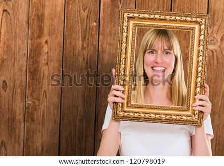 Portrait Of A Happy Woman Holding Frame against a wooden background - stock photo