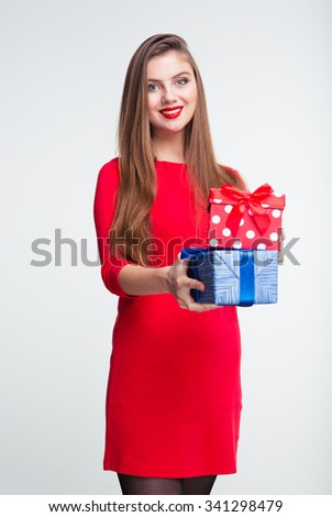 Portrait of a happy woman in red dress holding gift boxes isolated on a white background
