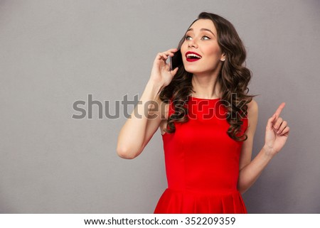 Portrait of a happy woman in red dress talking on the phone over gray background - stock photo
