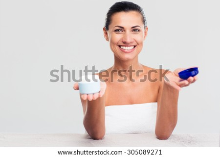 Portrait of a happy woman in towel sitting at the table and holding cream jar isolated on a white background