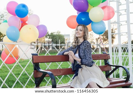 Portrait of a happy woman sitting in a park against the sunset, outdoors - stock photo