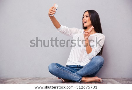 Portrait of a happy woman sitting on the floor and making selfie photo on smartphone on gray background - stock photo