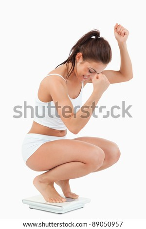 Portrait of a happy woman squatting on scales against a white background - stock photo