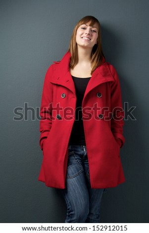 Portrait of a happy woman standing on gray background with red winter jacket - stock photo
