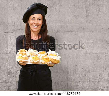 Portrait Of A Happy Woman While Holding Cupcake, Indoor - stock photo