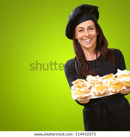 Portrait Of A Happy Woman While Holding Cupcake On Green Background - stock photo