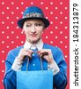 Portrait of a happy woman with a paper bag in her hands, red polka dot background - stock photo