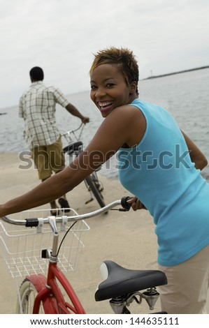 Portrait of a happy woman with bicycle and man in background on beach - stock photo