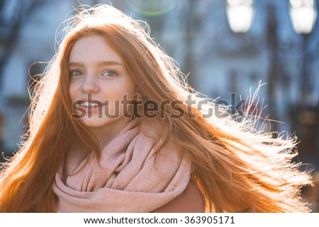 Portrait of a happy woman with long redhead hairs standing outdoors - stock photo