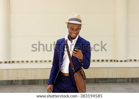 Portrait of a happy young african guy with bag and mobile phone - stock photo