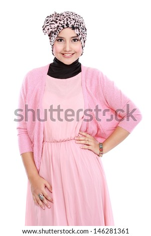 Portrait of a happy young asian muslim woman in action and looking at camera - stock photo