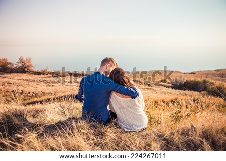 portrait of a happy young beautiful couple in love hugging and kissing at sunset outdoor - stock photo