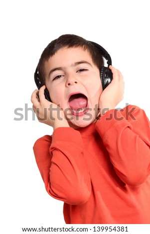 Portrait of a happy young boy listening to music on headphones - stock photo