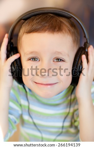 Portrait of a happy young boy listening to music on headphones ,little boy smiling baby with headphones,child holding hands headphones - stock photo