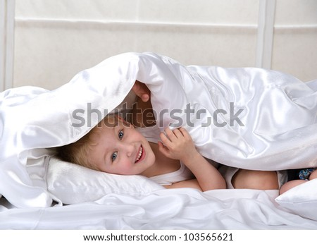 Portrait of a happy young boy under bedsheet - stock photo