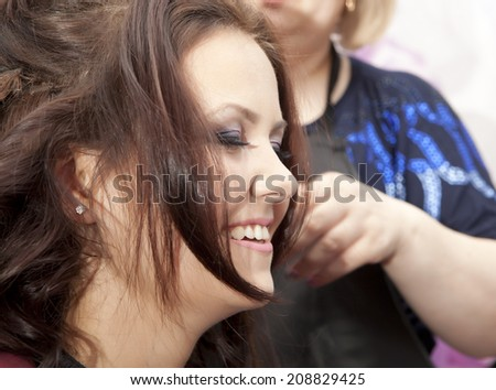 Portrait of a happy young brunette woman at the hair salon