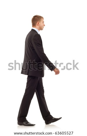 Portrait of a happy young business man walking on white background - stock photo