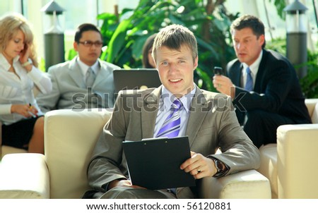 Portrait of a happy young business man with colleagues in the background - stock photo