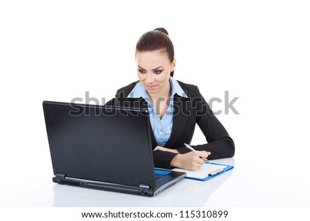 Portrait of a happy young business woman at the office desk taking notes from her laptop against white background - stock photo