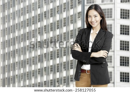 Portrait of a happy young business woman standing with folded hand against urban city background