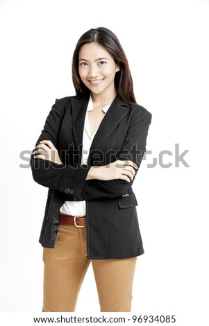 Portrait of a happy young business woman standing with folded hand against white background