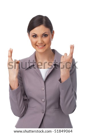 Portrait of a happy young business woman with fingers crossed on white - stock photo