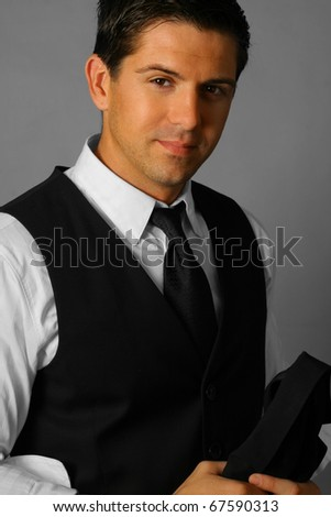 Portrait of a happy young businessman holding jacket against gray background - stock photo