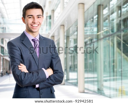 Portrait of a happy young businessman in suit standing at office - stock photo