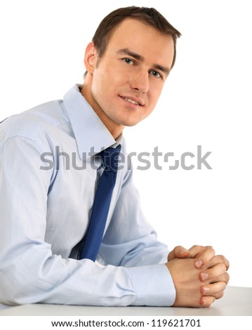 Portrait of a happy young businessman sitting on the desk