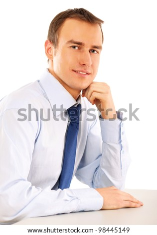 Portrait of a happy young businessman sitting on the desk, isolated on white background - stock photo