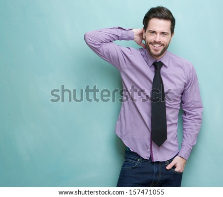 Portrait of a happy young businessman smiling against blue background - stock photo