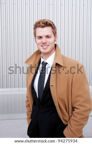 Portrait of a happy young businessman with trench coat - stock photo