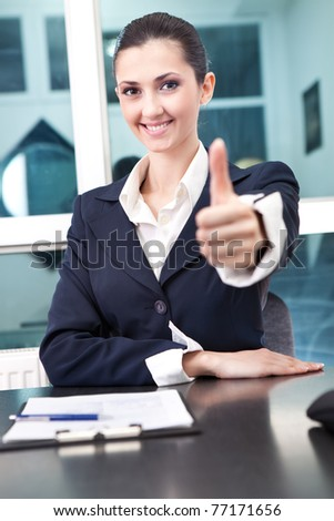 portrait of a happy young businesswoman showing thumb up sign - stock photo