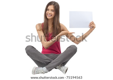 Portrait of a happy young casual woman sitting and holding a blank signboard, isolated on white background - stock photo