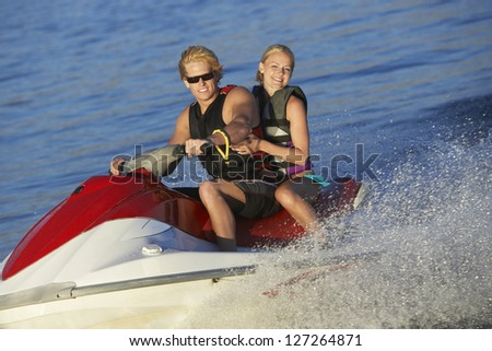 Portrait of a happy young caucasian couple riding jet ski on lake - stock photo