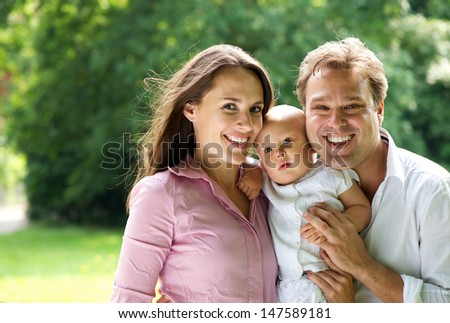 Portrait of a happy young caucasian family holding baby - stock photo