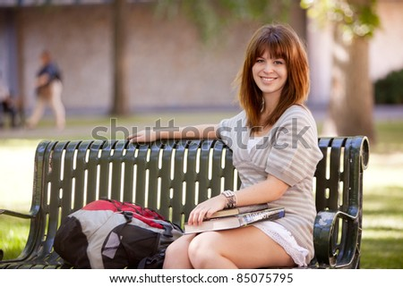 Portrait of a happy young college girl outdoors on a bench - stock photo