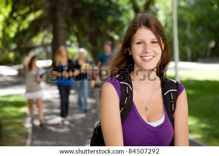 Portrait of a happy young college girl with friends in background - stock photo