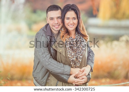 Portrait of a happy young couple embracing and looking at camera while walking in a park - stock photo