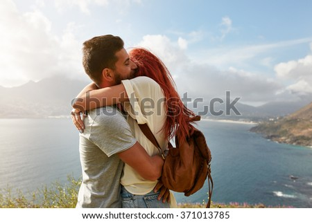 Portrait of a happy young couple enjoying a romantic embrace outdoors. Young man hugging his girlfriend while standing on a hill top with seascape in background. - stock photo