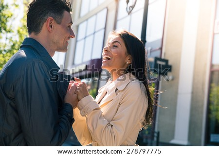 Portrait of a happy young couple flirting and looking to each other outdoors - stock photo
