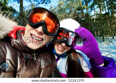 Portrait of a happy young couple having a rest in winter park. - stock photo
