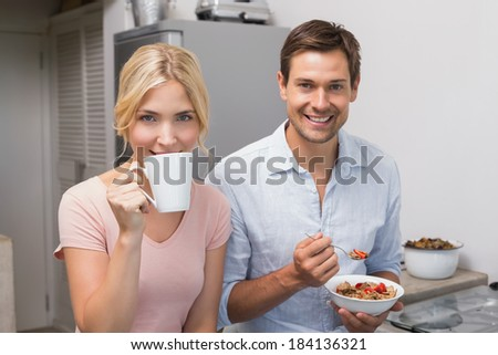 Portrait of a happy young couple having breakfast at home - stock photo