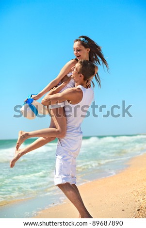 Portrait of a happy young couple having fun on the beach. - stock photo