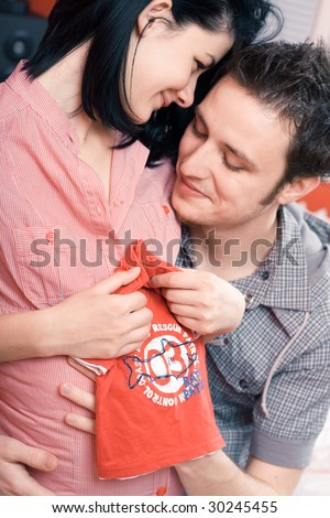 Portrait of a happy young couple holding a red shirt for their unborn child - stock photo